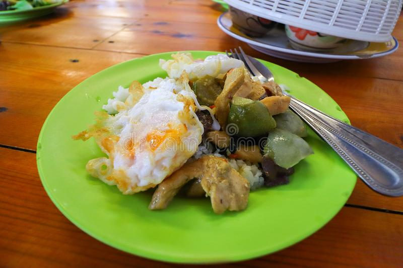 Thai a la carte, Thai food, rice with green curry with chicken and fried egg toping. Thai a la carte. Thai food. Rice with green curry with chicken and fried egg stock image