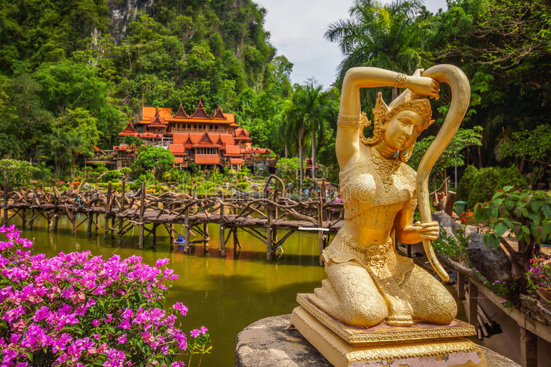 Thai literature golden Goddess of the earth statue. Thai literature Goddess of the earth statue twisting her hair in front of Thailand rural Buddhist temple royalty free stock photo