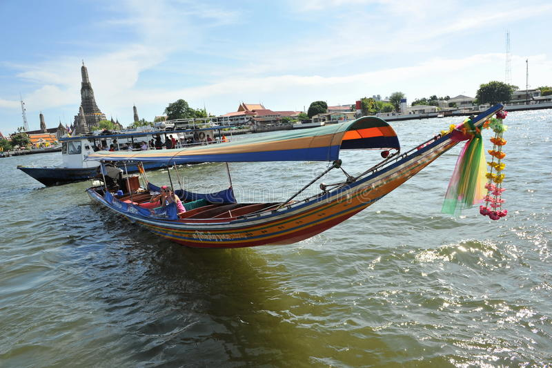 Thai Long-Tail Boat. A long-tail boat carrying tourists sits on the Chao Praya River on April 5, 2012 in Bangkok, Thailand. Long-tail boats are a cheap form of stock photo