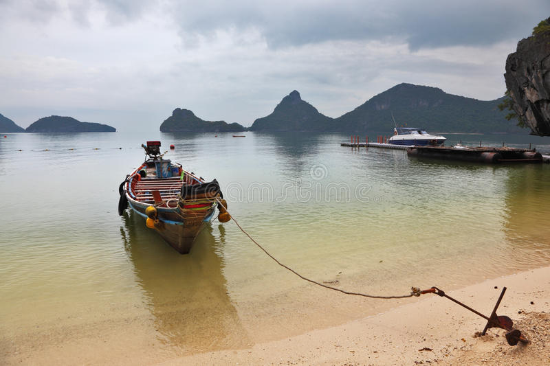 Thai Longtal boat moored with an anchor royalty free stock photos