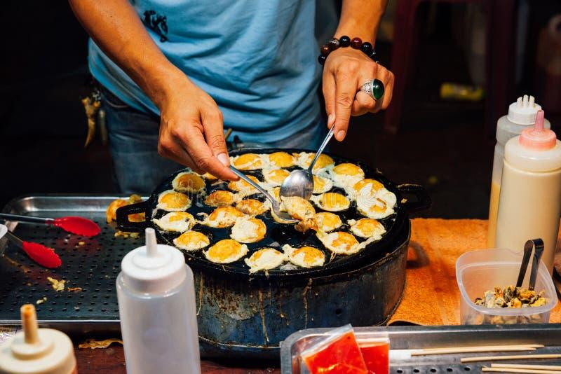 Thai man cook quail eggs stock photo