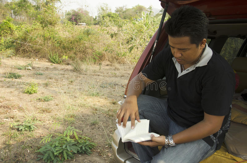 Thai man people sitting on car and read novel for relax at outdo. Or in Ratchaburi,Thailand stock photography