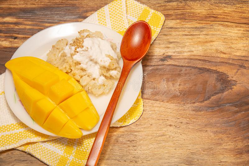 Thai mango and sticky rice with coconut milk desserts on white dish with wooden background. Mango is Thailand`s tropical fruit. Top view stock photo