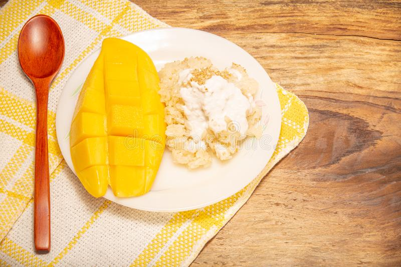 Thai mango and sticky rice with coconut milk desserts on white dish with wooden background. Mango is Thailand`s tropical fruit. Thai mango and sticky rice with stock image