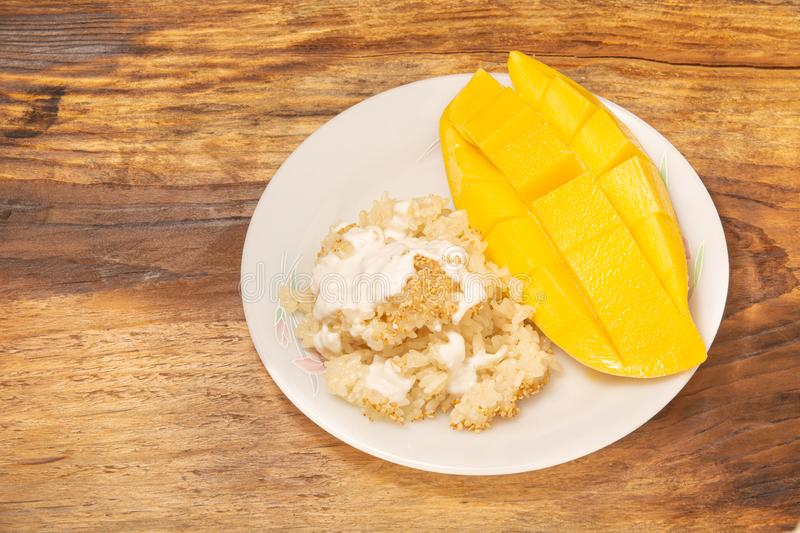 Thai mango and sticky rice with coconut milk desserts on white dish with wooden background. Mango is Thailand`s tropical fruit. Top view royalty free stock images