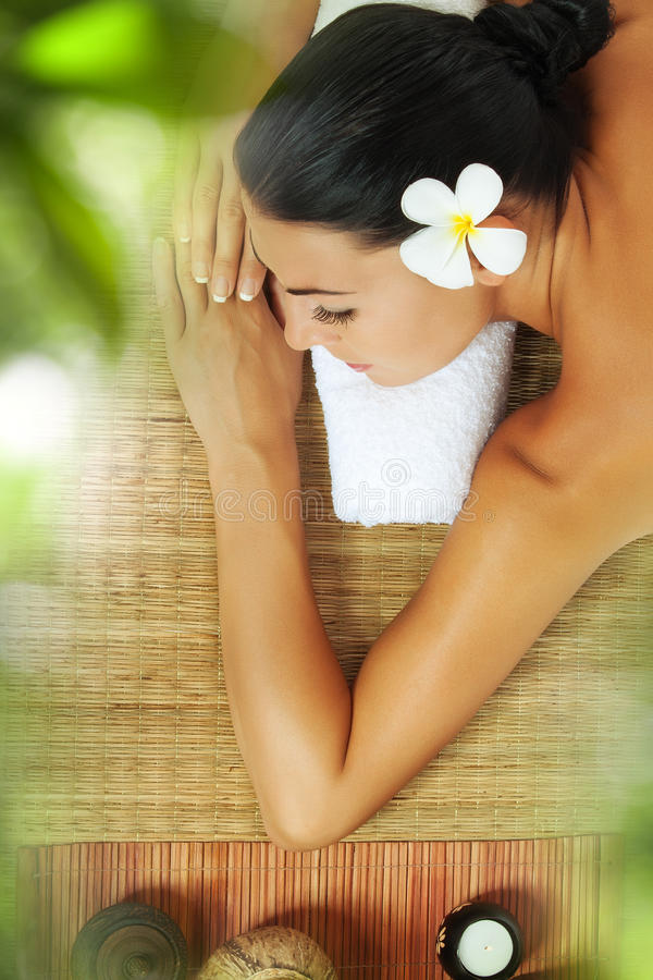 Thai massage. Portrait of young beautiful woman relaxing in spa environment royalty free stock images