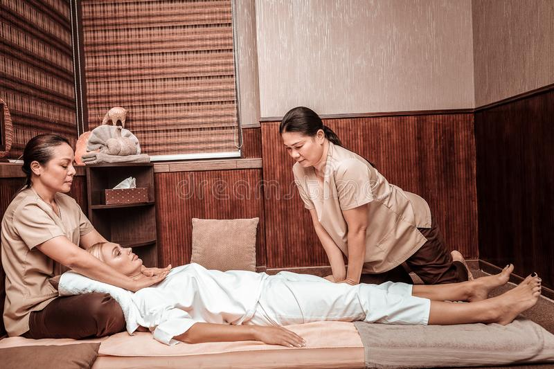 Two masseuses helping their client to relax. Thai massage salon. Two concentrated masseuses helping their calm client to relax massaging her neck and legs royalty free stock photography