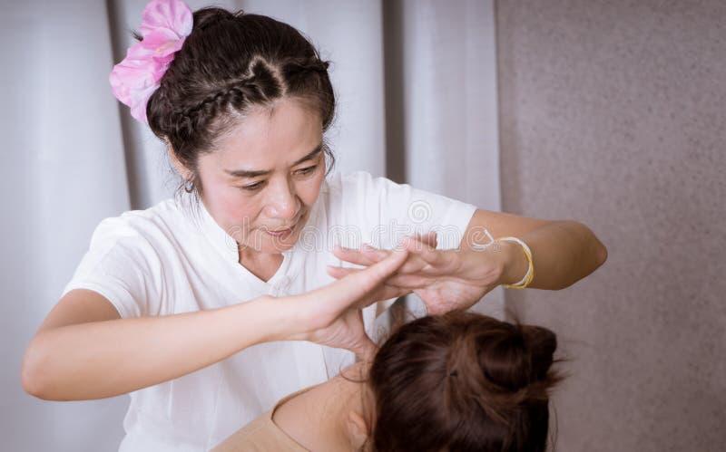 Thai Massage Therapist is giving neck massage. To a women stock photos