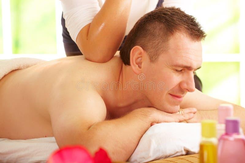Thai massage treatment. Male enjoying kind of Thai massage treatment with female hand on back royalty free stock image