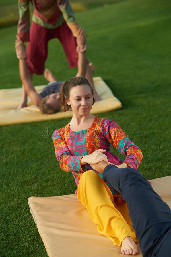 Thai massage yoga exercise. Summer thai feet massage practise outdoor royalty free stock photos