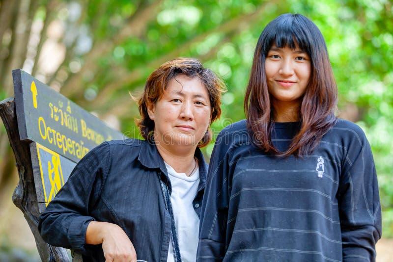 Thai mother and her daughter standing and hugging on the stone of Saiyoke waterfall. Kanchanaburi, Thailand February 15, 2012 stock photos