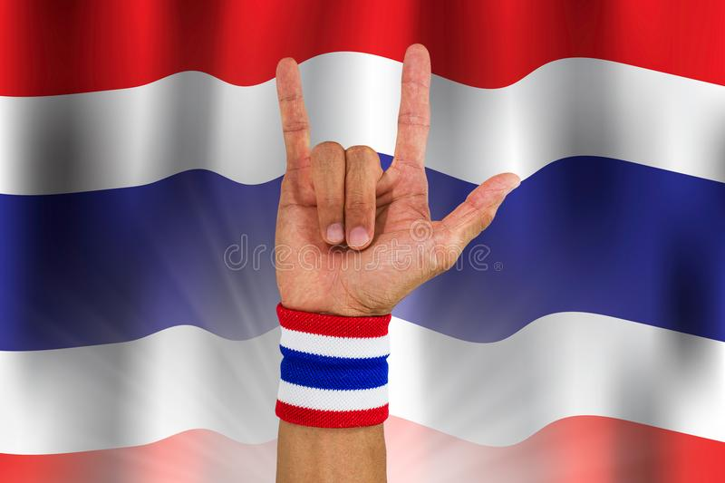 Thai national color cloth wristband on the guy`s wrist making I love you sign on waving national Thailand flag background. Thai national color cloth wristband royalty free illustration