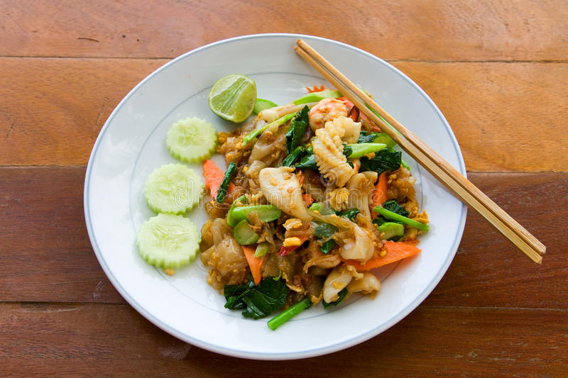 Thai noodle with seafood. On white plate with chopsticks stock image