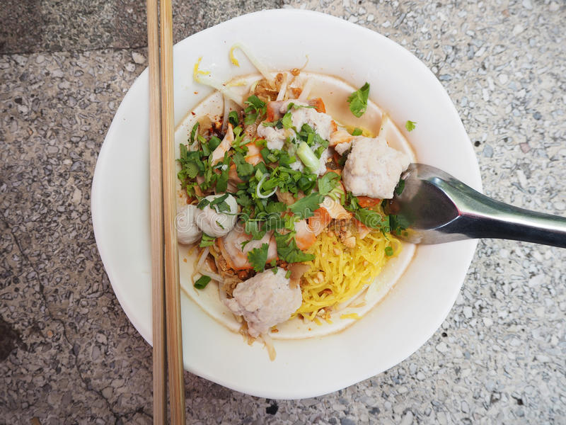 Thai Noodle. Thai yellow noodle with white bowl, spoon and chopsticks royalty free stock images