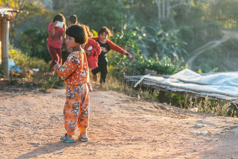 Thai northern kid wearing pyjamas standing with sunlight and her friends in the background in the Akha village of Maejantai. royalty free stock photos