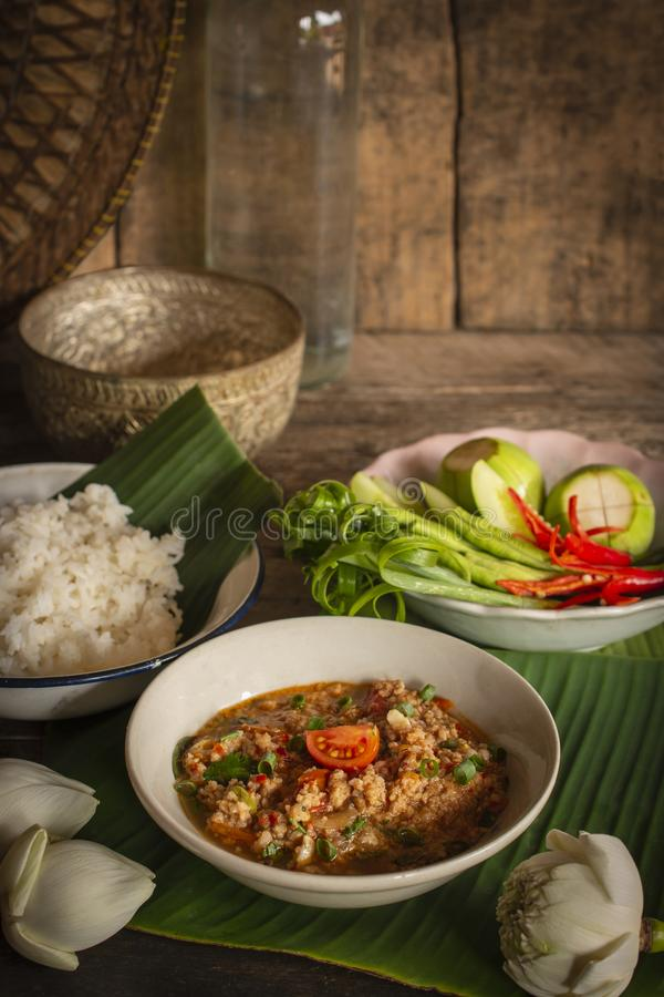 Thai Northern Style Pork and Tomato Chili Relish, nam prik ong in white bowl on wood table there are side dishes of fresh royalty free stock photography