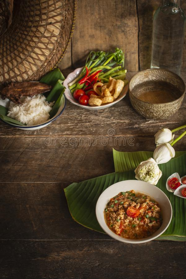 Thai Northern Style Pork and Tomato Chili Relish, nam prik ong in white bowl on wood table there are side dishes of fresh stock images