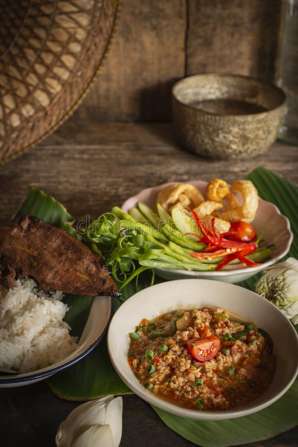 Thai Northern Style Pork and Tomato Chili Relish, nam prik ong in white bowl on wood table there are side dishes of fresh stock photos