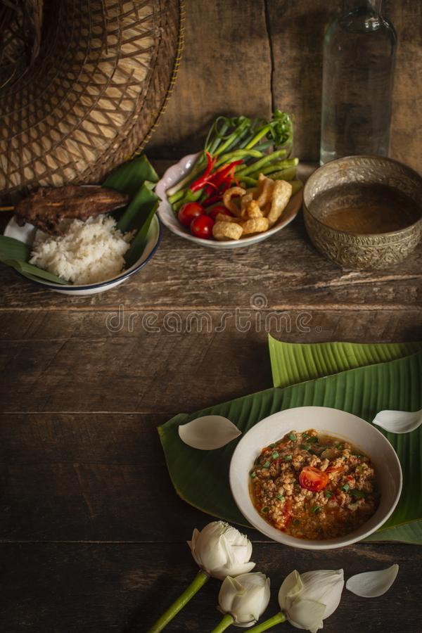 Thai Northern Style Pork and Tomato Chili Relish, nam prik ong in white bowl on wood table there are side dishes of fresh stock photo