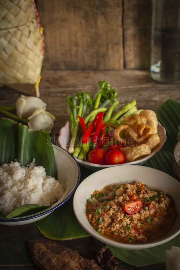 Thai Northern Style Pork and Tomato Chili Relish, nam prik ong in white bowl on wood table there are side dishes of fresh royalty free stock images