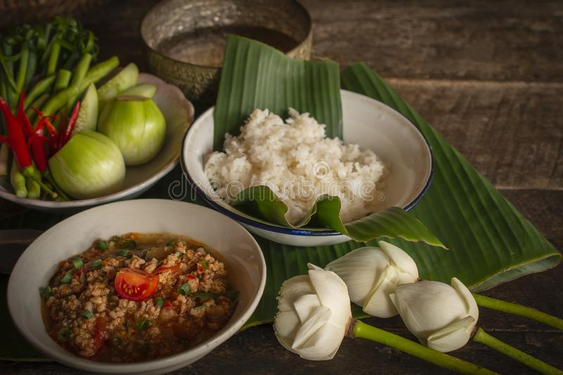 Thai Northern Style Pork and Tomato Chili Relish, nam prik ong in white bowl on wood table there are side dishes of fresh royalty free stock photo