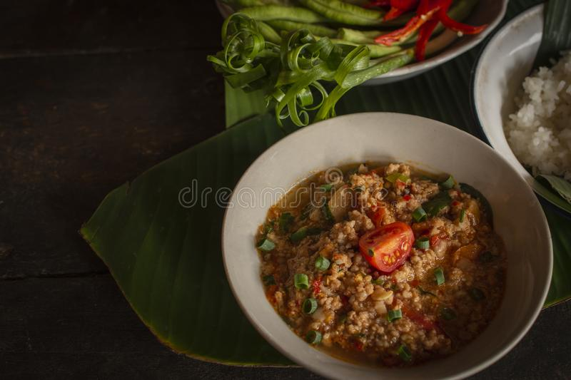 Thai Northern Style Pork and Tomato Chili Relish, nam prik ong in white bowl on wood table there are side dishes of fresh. Vegetables and cooked rice placed royalty free stock image