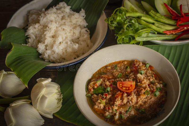 Thai Northern Style Pork and Tomato Chili Relish, nam prik ong in white bowl on wood table there are side dishes of fresh royalty free stock photos