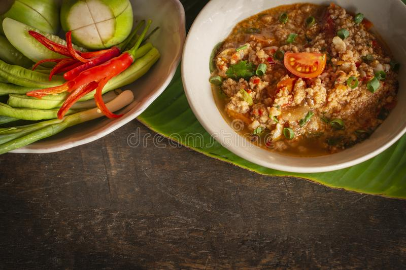 Thai Northern Style Pork and Tomato Chili Relish, nam prik ong in white bowl on wood table there is side dishes of fresh royalty free stock photography