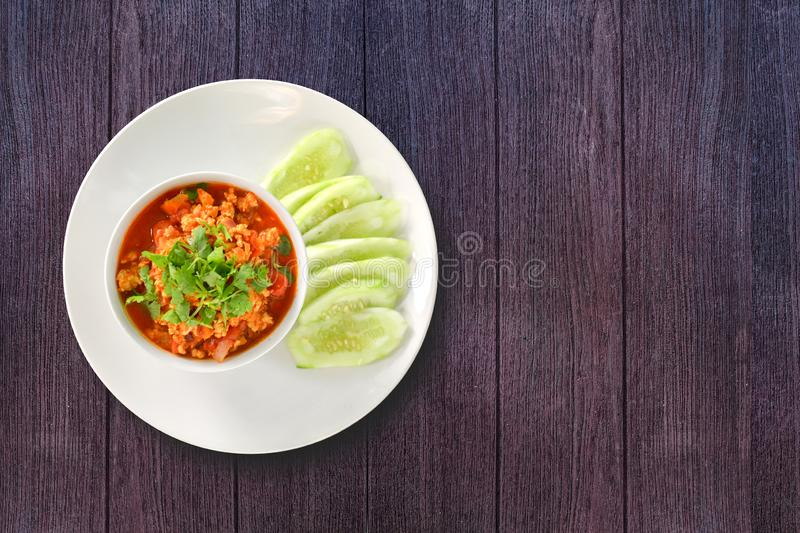 Thai Northern Style Pork and Tomato Relish in white bowl served with cucumber sliced on dark wooden background. Hot and spicy. Dipping. Top view royalty free stock photography