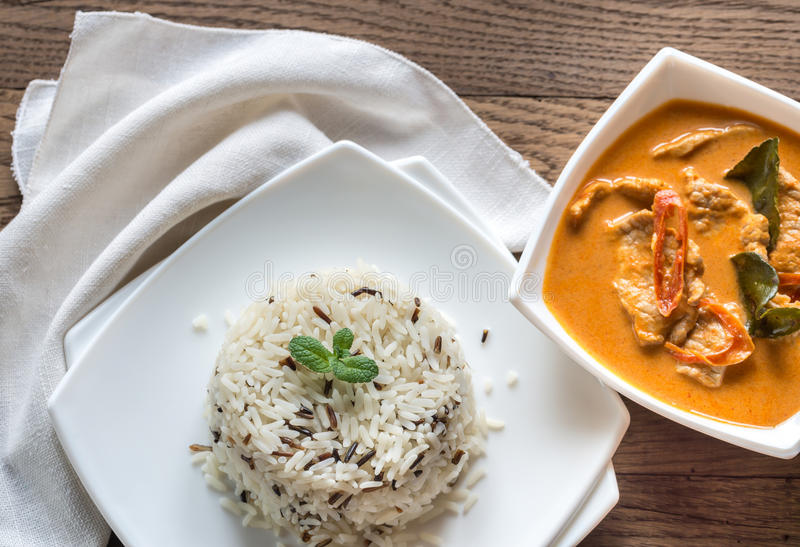Thai panang curry with bowl of white and wild rice. Portion of thai panang curry with bowl of white and wild rice on the wooden table stock photo