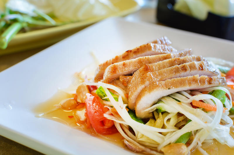 Thai papaya salad on white dish with grilled pork stock images