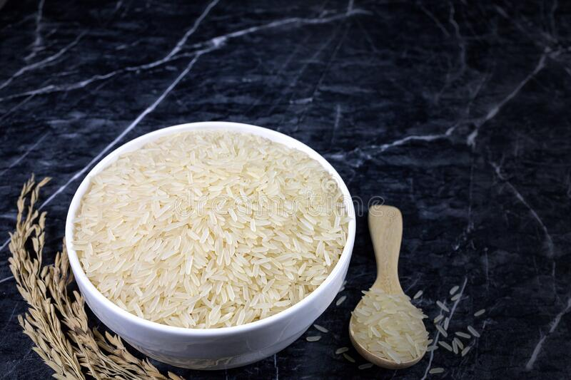 Thai parboiled rice  in white ceramic bowl and wooden spoon on dark marble table.  stock photography