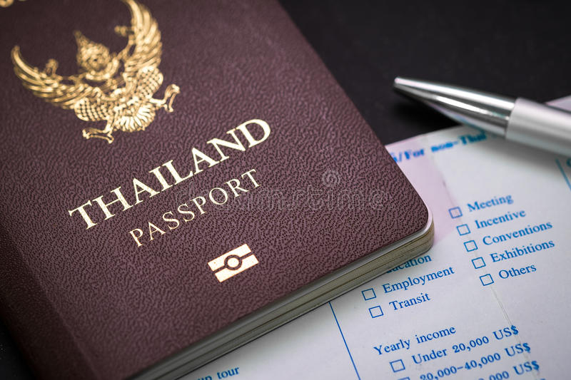 Thai Passport and customs form and pen on table. Thai Passport and customs form and pen. concept of travel and business stock photography