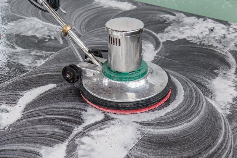 Thai people cleaning black granite floor with machine and chemical. Cleaning black granite floor with machine and chemical royalty free stock image