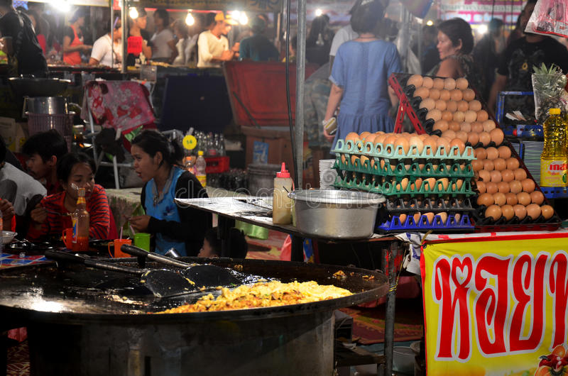 Thai people cooking Fried mussel with egg and crispy flour or Oyster omelette. For sale people in market fair in annual festival of Wat Lam Pho on February 6 royalty free stock photo