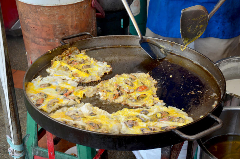 Thai people cooking Fried mussel with egg and crispy flour. Or Oyster omelette for sale people in market royalty free stock photos