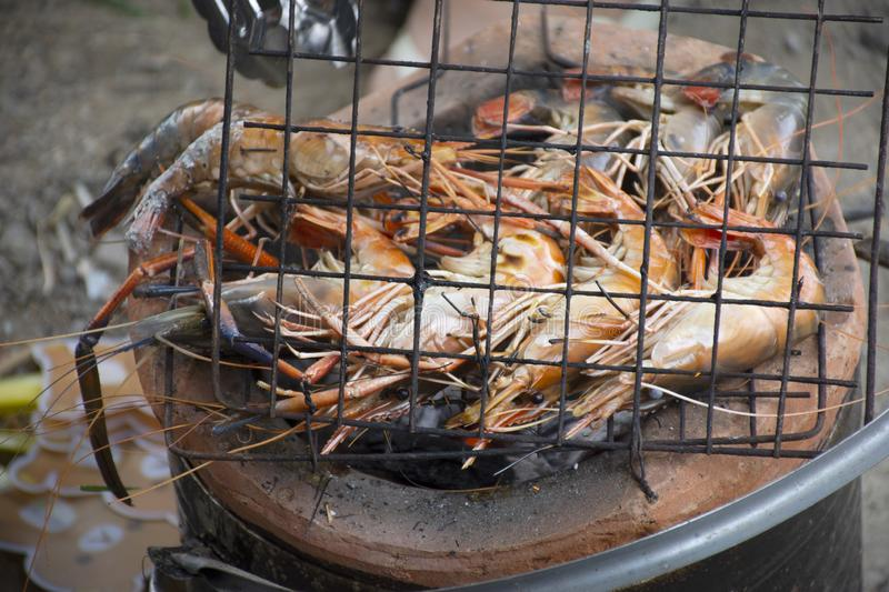 Thai people cooking grill shrimp or prawn on stove. Retro thai style at outdoor in Nonthaburi, Thailand stock image
