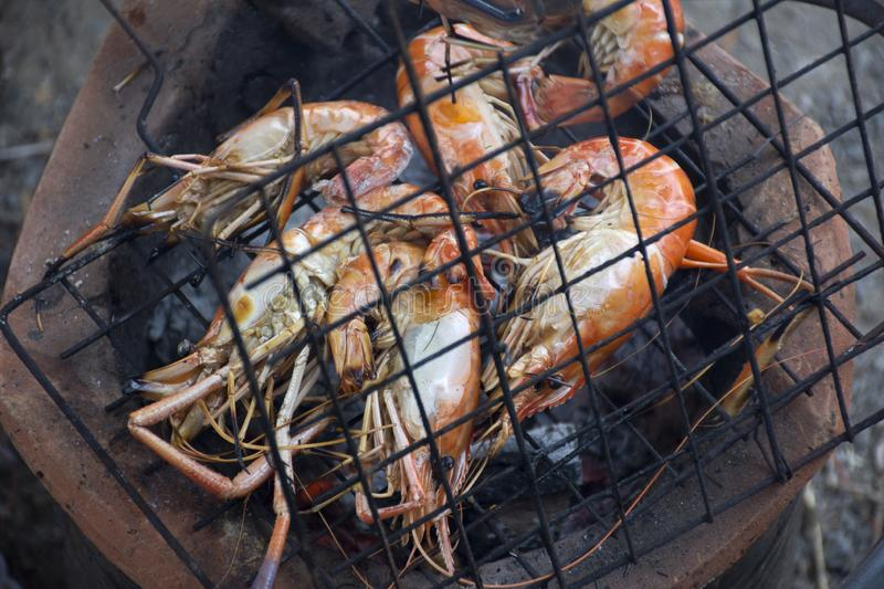Thai people cooking grill shrimp or prawn on stove. Retro thai style at outdoor in Nonthaburi, Thailand stock images