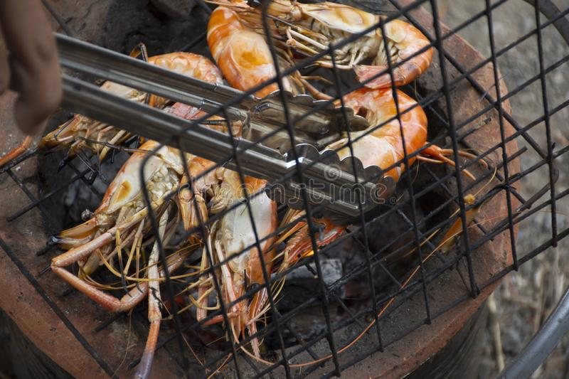 Thai people cooking grill shrimp or prawn on stove. Retro thai style at outdoor in Nonthaburi, Thailand royalty free stock images