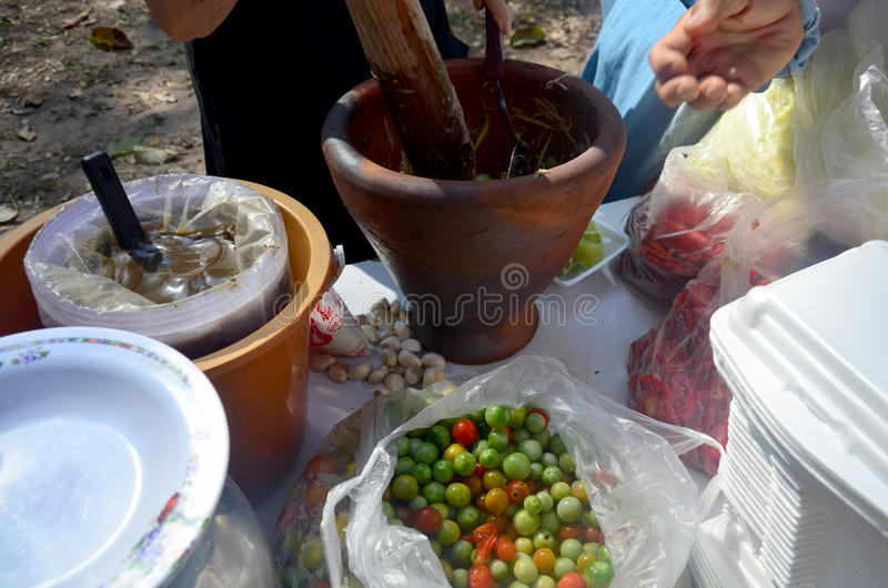 Thai people cooking thai cuisine Som Tum or thai food fruit spic. Y papaya salad with pickled fish and Turkey berry or Solanum torvum and small eggplant and royalty free stock image