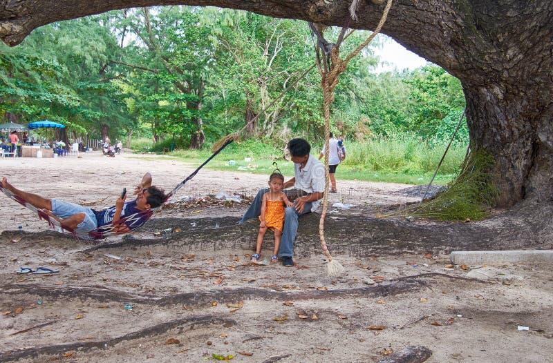 Thai people having a rest under shadow of old tree near Kata beach on Phuket, Thailand. PHUKET, THAILAND - NOVEMBER 06, 2014: Thai people having a rest under stock photography