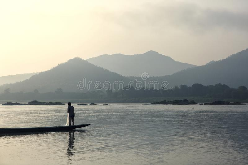 Thai people is highly skilled fishermen. Man stands on the end of long narrow pirogues to cast his nets. View of mountain and river, natural background stock image