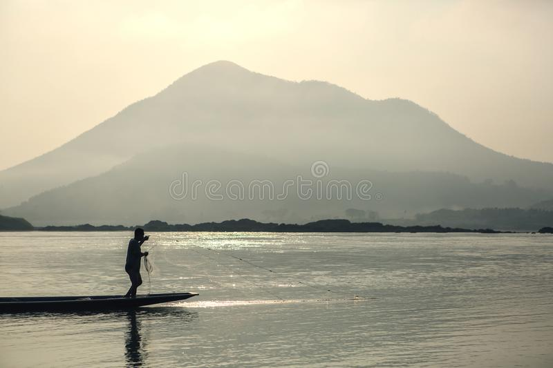 Thai people is highly skilled fishermen. Man stands on the end of long narrow pirogues to cast his nets. View of mountain and river, natural background royalty free stock photo