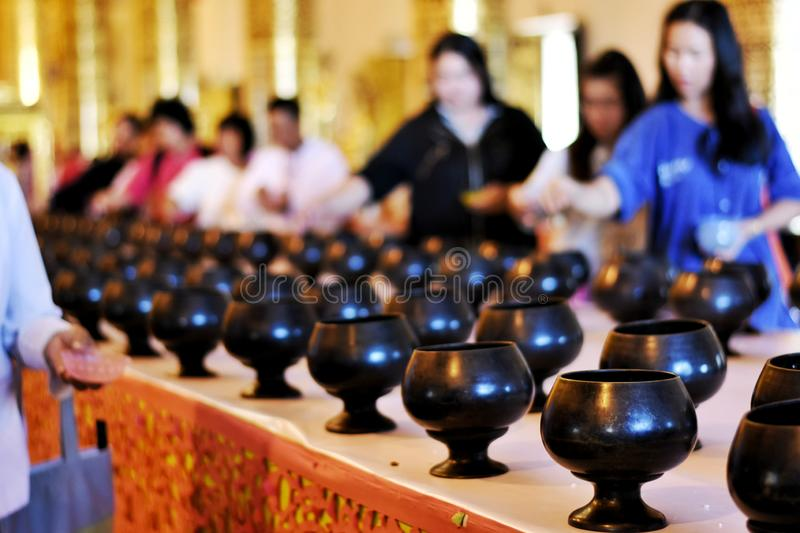 Thai people made the merit in the building of a temple for illustration Buddhism ceremony concept. Selective focus and bright perspective image of Thai people stock image
