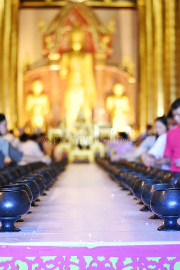 Thai people made the merit in the building of a temple for illustration Buddhism ceremony concept. Selective focus and bright perspective image of Thai people stock photos