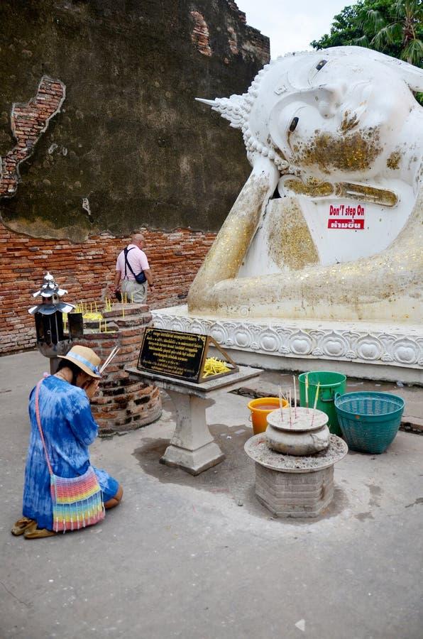 Thai people pray with flower, joss stick and candle for Buddha s. Thai people pray with flower, joss stick and candle for Reclining Buddha Statue at Wat Yai royalty free stock image