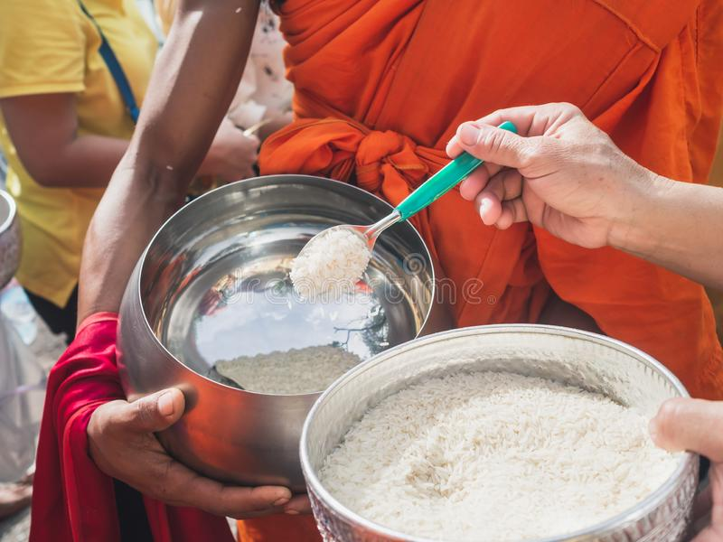 Thai people put food to a monk`s alms bowl in the end of Buddhist Lent Day royalty free stock photography
