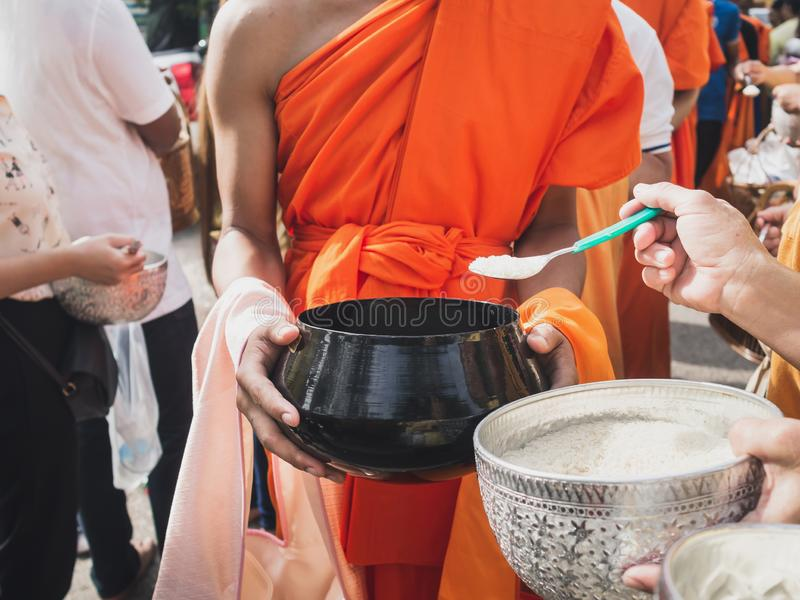 Thai people put food to a monk`s alms bowl in the end of Buddhist Lent Day.  royalty free stock image