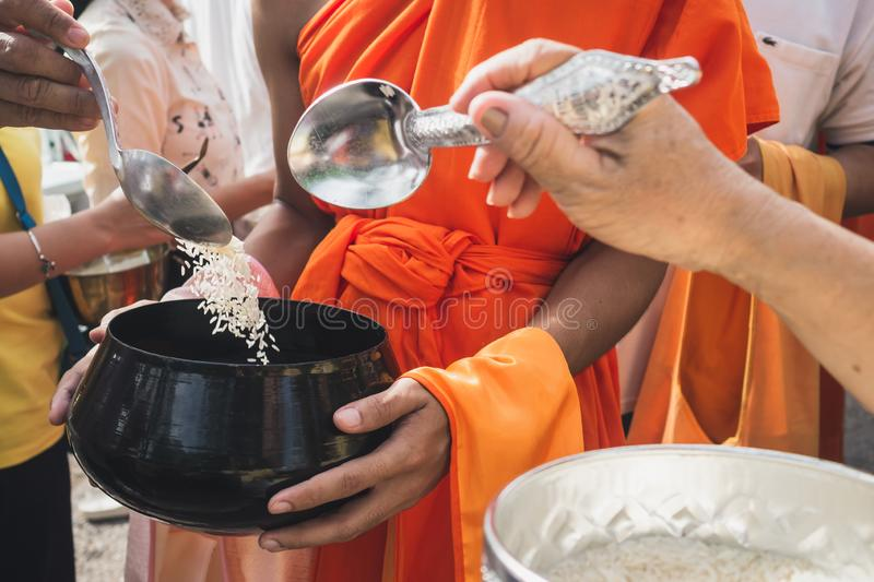 Thai people put food to a monk`s alms bowl in the end of Buddhist Lent Day stock photo