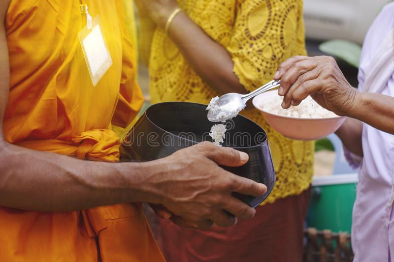Thai people put food to a monk`s alms bowl in the end of Buddhist Lent Day.  royalty free stock images